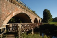Footbridge and railway bridge over River Mole north of Box Hill and Westhumble railway station, Dorking